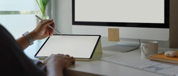 空白の画面のタブレットとウィンドウの横にあるシンプルなオフィスの机の上のコンピューターを扱う男性起業家
