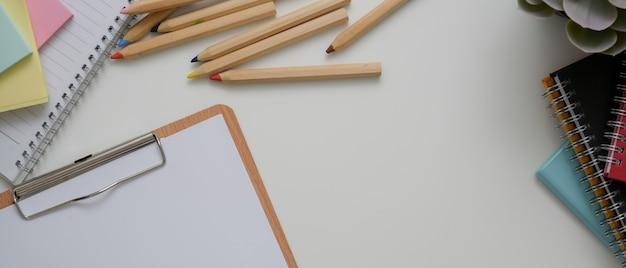 Белый офисный стол с бумагой в буфер обмена, канцелярские принадлежности, другие офисные принадлежности и копией пространства