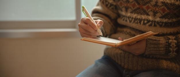 Девушка пишет на тетради дневника, сидя в углу чтения рядом с окном