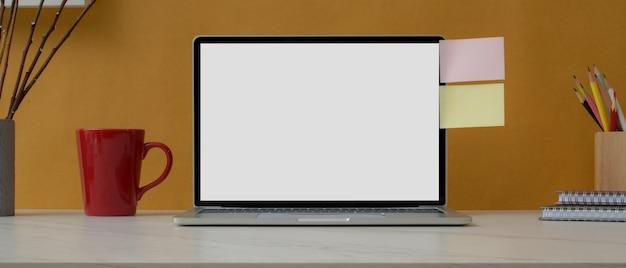 空白の画面のラップトップ、文房具、マグカップ、白いテーブルに付箋のホームオフィスデスク