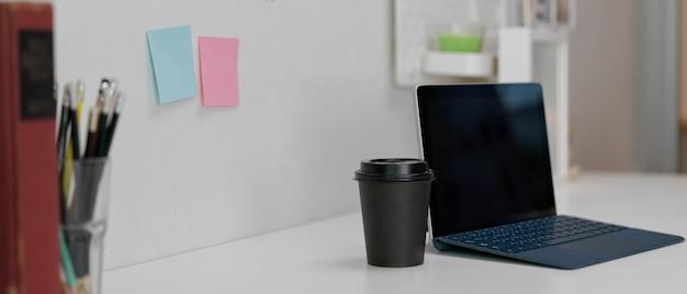 ワイヤレスキーボード、紙コップ、白いモダンな作業台に文房具のデジタルタブレット