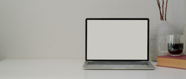 ラップトップ、本、コーヒーカップ、装飾、白い机の上のコピースペースを持つシンプルなホームオフィス