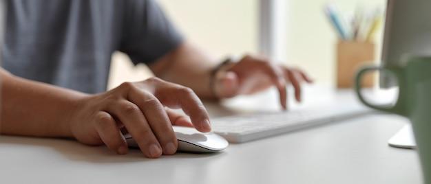 マグと供給の白いオフィスの机の上のコンピューターデバイスを使用して男性労働者