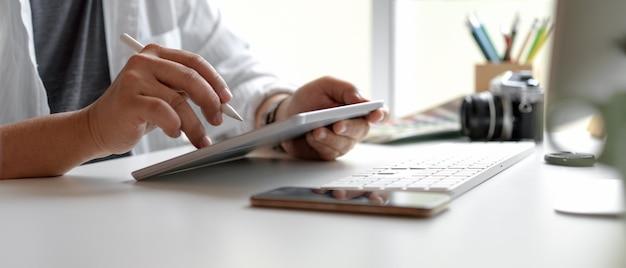スマートフォン、コンピューターデバイスおよび他の供給の白いオフィスの机の上のスタイラスペンでデジタルタブレットを使用して男性デザイナー