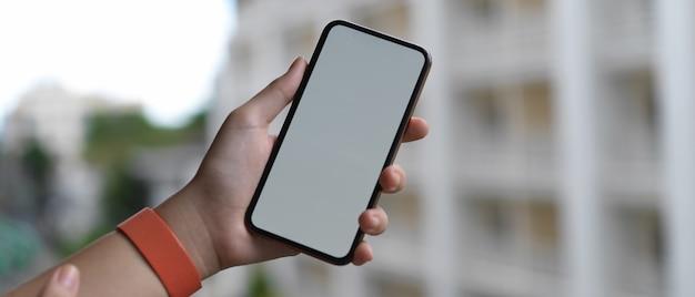 バルコニーに立っている間空白の画面のスマートフォンを持っている手