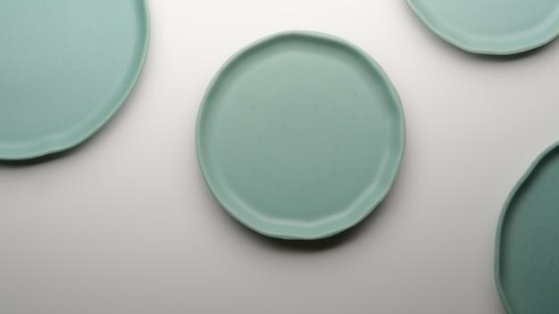 ターコイズブルーのセラミックプレートと白いダイニングテーブルの上のコピースペース