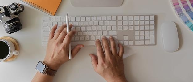 コンピューター、カメラ、コーヒーカップと白いオフィスの机の上のラップトップで働く男性起業家