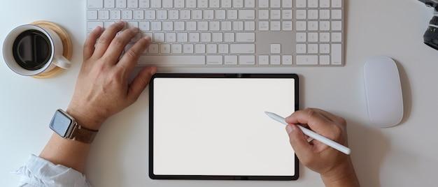 空白の画面のタブレットを使用して、白いオフィスの机の上のコンピューターデバイスを操作するビジネスマン