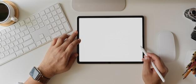 コンピューターデバイスと他の供給の白いオフィスの机の上のスタイラスと空白の画面のタブレットを使用するビジネスマン