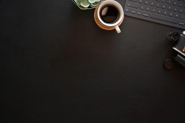 キーボードタブレットとビンテージカメラとダークレザーオフィス写真デスクテーブル