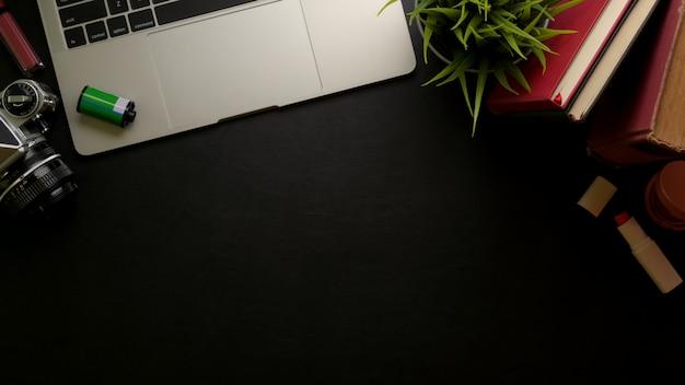 コピースペース、ラップトップ、カメラ、消耗品、化粧品、黒いテーブルの装飾が施されたフェミニンなスタイリッシュなオフィスデスク