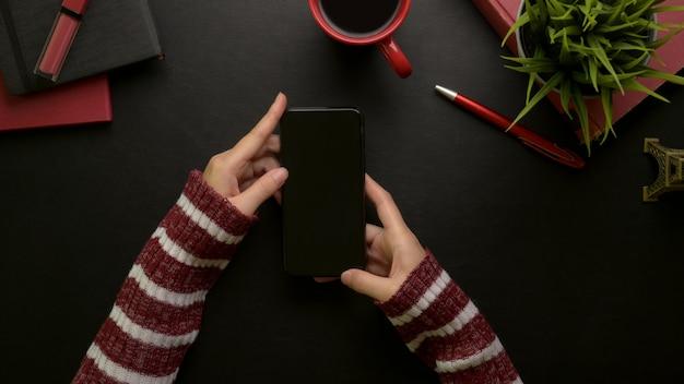 化粧品、消耗品、コーヒーカップ、装飾のスタイリッシュなオフィスの机に座っている間スマートフォンを使用している女性