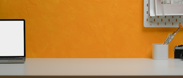コピースペース、ラップトップ、ペイントブラシ、黄色の壁の棚が付いている創造的なホームオフィスの机