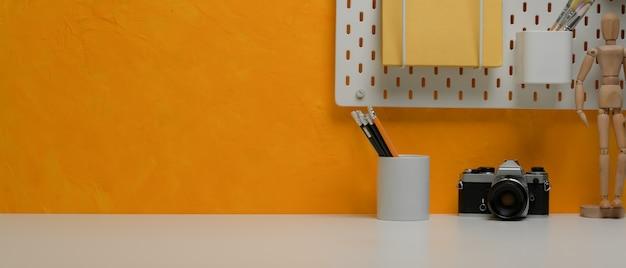 黄色の壁に文房具、カメラ、文房具、棚を備えたスタイリッシュなワークスペースにスペースをコピー
