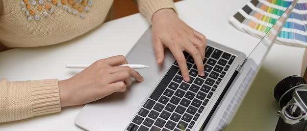 カメラとコーヒーカップと白いオフィスの机の上のラップトップに入力する女性デザイナー