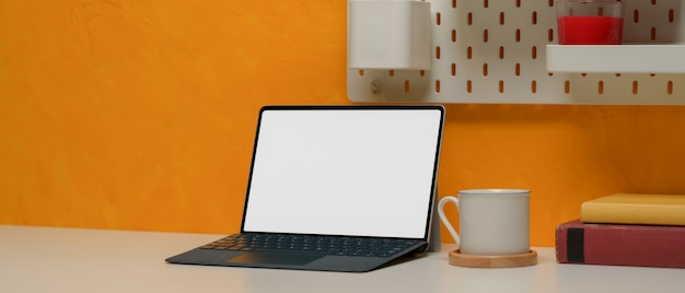 カップ、コピースペース、書籍、黄色の壁の棚とスタイリッシュなワークスペースをタブレットします。