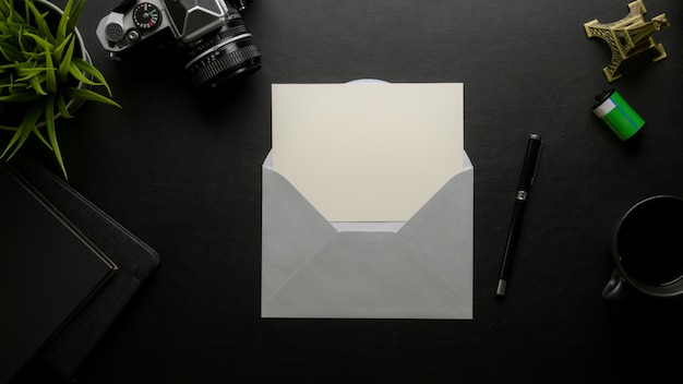 デジタルカメラと事務用品の暗いオフィスの机の上の灰色の封筒で開いたグリーティングカード