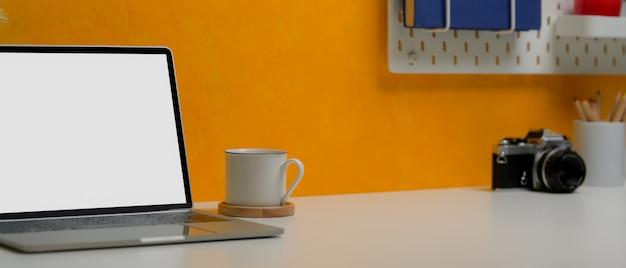 ノートパソコン、コーヒーカップ、コピースペース、カメラ、消耗品を備えたスタイリッシュなワークスペース
