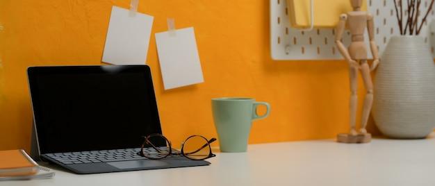 デジタルタブレット、メガネ、マグカップ、白い机の上の装飾のスタイリッシュなワークスペース