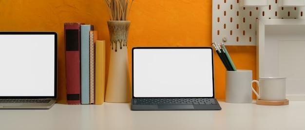 本、文房具および装飾が付いている創造的なホームオフィスの机の上のブランクスクリーンのタブレットそしてラップトップ