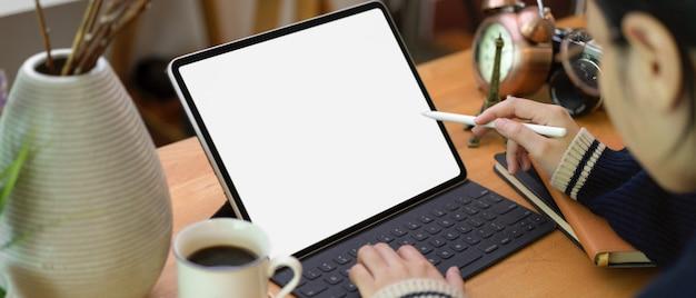 コーヒーカップと装飾のホームオフィスの机の上のタブレットで描く女性フリーランサー