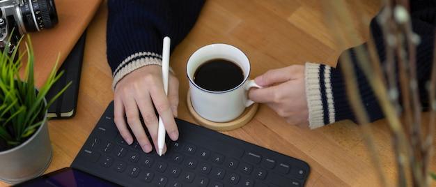 デジタルタブレットのキーボードで入力する女性のフリーランサーの右手とコーヒーカップを保持している左手