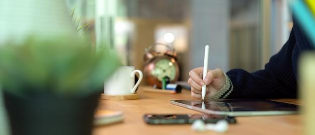 スマートフォン、消耗品、装飾の木製ホームオフィスの机の上のスタイラス付きデジタルタブレットを使用して女性の手
