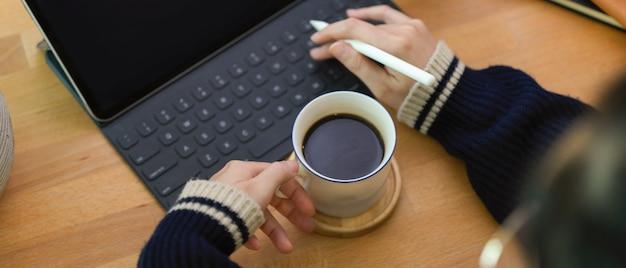 作業台の上にデジタルタブレットを使用してコーヒーカップと右手を持つ女性の左手