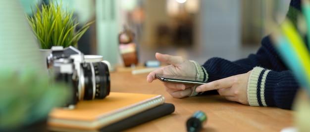 カメラと用品の木製ホームオフィスの机の上のスマートフォンを保持している女性の手