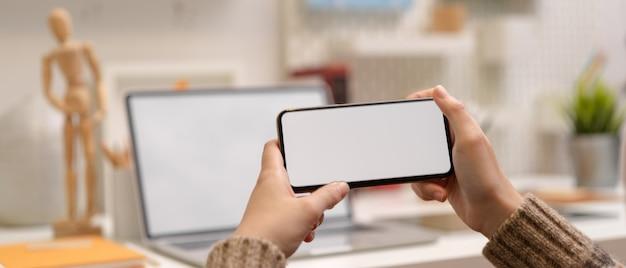 Женский дизайнер отдыхает и смотрит видео на горизонтальном макете смартфона, сидя за рабочим столом