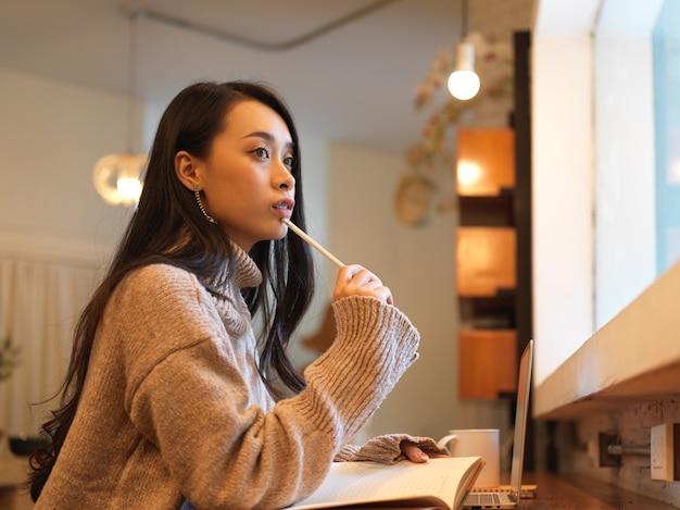 Вид сбоку женщины, сидящей на деревянной стойке в кафе, думая и смотрящей в окно во время чтения книги