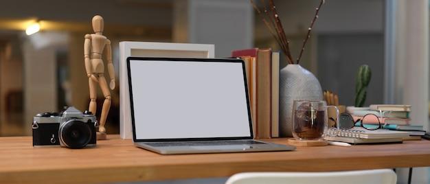 Обрезанный снимок рабочего места с пустым экраном ноутбука, книг, принадлежностей и украшений на деревянном столе в гостиной