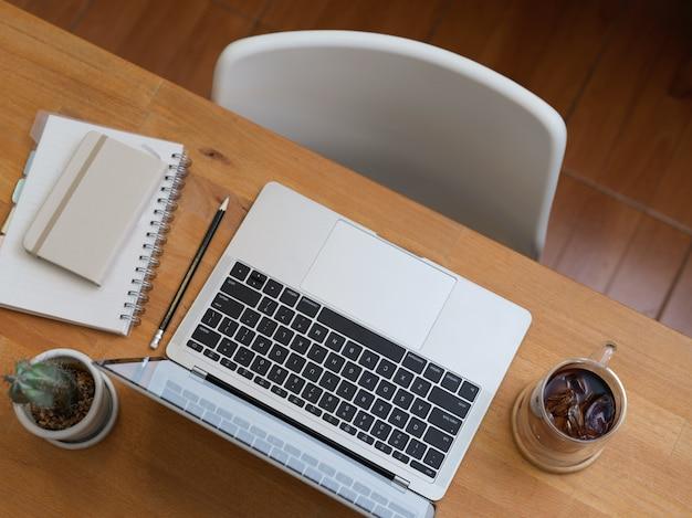 Вид сверху офисного стола с ноутбуком, карандашом, дневником, горшком с кактусом и белым стулом в офисной комнате