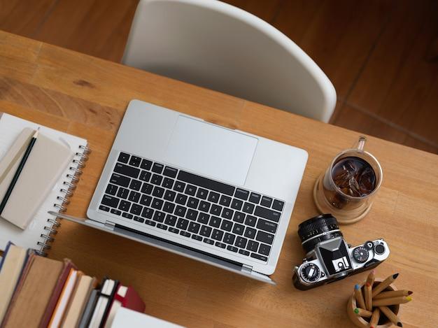 Вид сверху офисного стола с ноутбуком, расходными материалами, камерой, книгами и белым стулом в офисной комнате