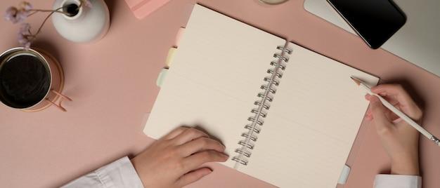Снимок женщины, пишущей на пустом блокноте на розовом столе с принадлежностями и украшениями