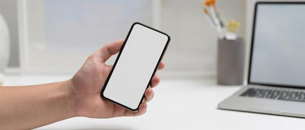 ホームオフィスルームのラップトップで作業テーブルでクリッピングパスを持つスマートフォンを持っている男性の手のクローズアップ表示