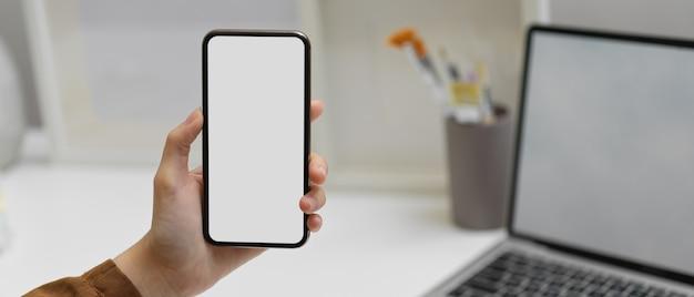ホームオフィスルームのラップトップで作業テーブルでクリッピングパスを持つスマートフォンを持っている女性の手のクローズアップ表示