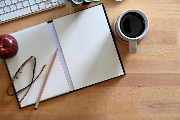 木製のワークスペースの机とコピースペースにキーボードコンピューターとノート。
