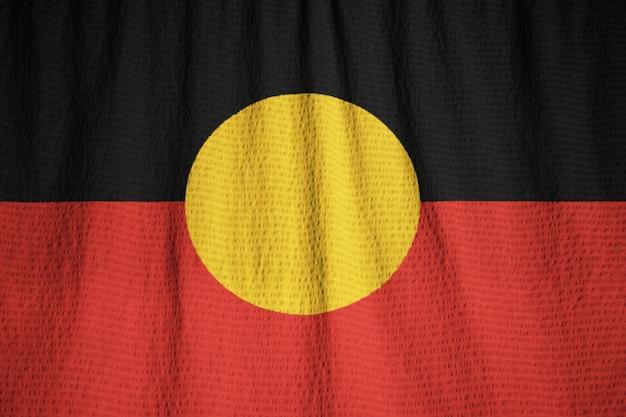 Макрофотография взломанный австралийский флаг аборигенов, австралийский флаг аборигенов, дующий в ветре