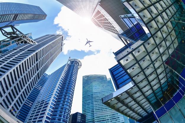 シンガポールの中央ビジネス地区の高層ビル間を飛ぶ飛行機。