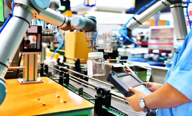 エンジニアのチェックと制御の自動化ロボットアームがガラスの水筒を配置