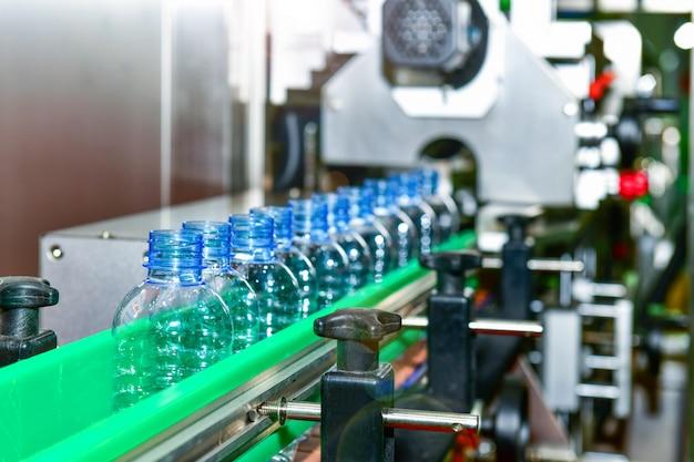 パッケージ用の自動化されたコンベアシステムの産業オートメーションで透明なプラスチックボトルを転送
