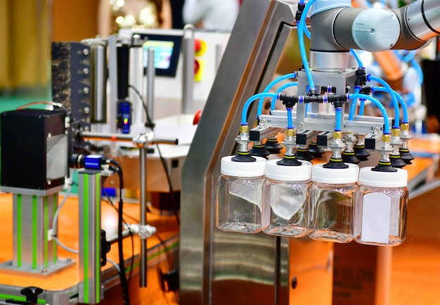 ロボットアームは、生産ライン工場の自動産業機械装置にガラス製の水ボトルを配置
