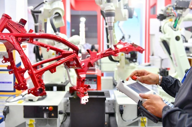 エンジニアのチェックと制御の自動化工場でのオートバイプロセスの自動車構造用のロボットアームマシン。