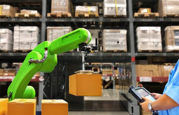 ボックスと在庫棚の背景にコントロールパネルでロボットマシンを操作する労働者を保持している産業用ロボット