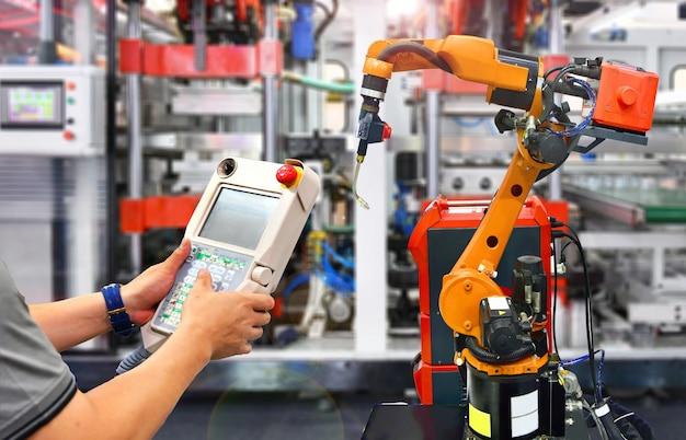 オレンジ色の近代的なロボットシステム工場、産業用ロボットのエンジニアチェックおよび制御自動化。