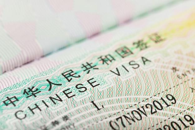中国のバックグラウンドでの旅行のための中国のビザのクローズアップ