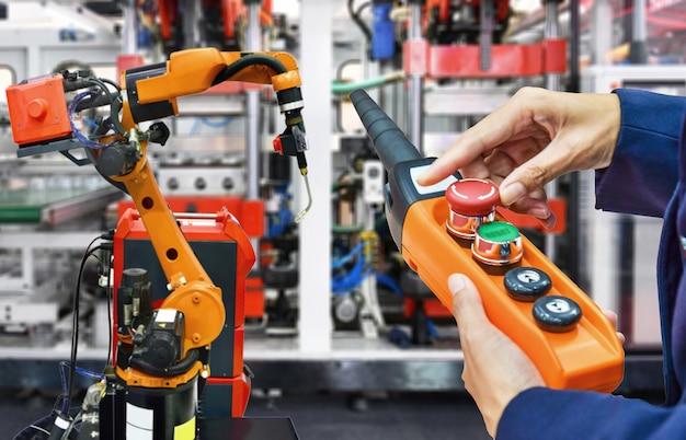 Инженер проверяет и контролирует современные высококачественные средства автоматизации сварочных роботов на промышленных