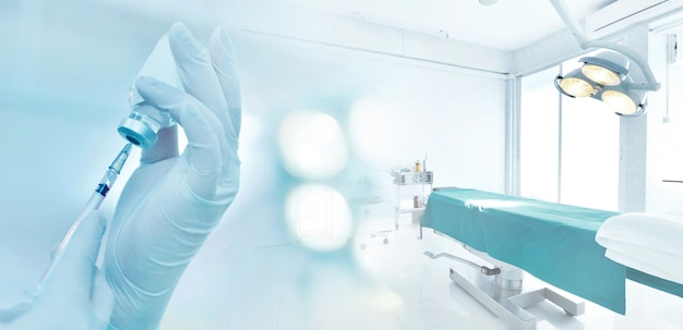 注射器と薬瓶を持っている手が青いトーンの手術室で注射の準備をする