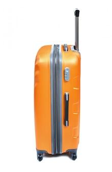 白で隔離されるオレンジ色のスーツケースの横に